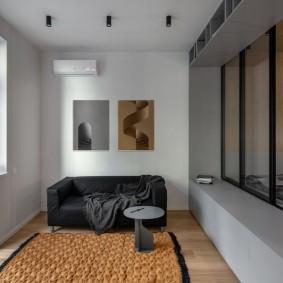 Черный диванчик в комнате с выходом на балкон