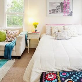 Комфортная кровать перед окном светлой комнаты