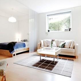 Небольшое окно над диваном в спальне-гостиной