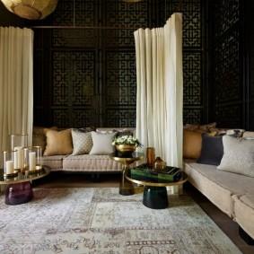 Угловой диван в гостиной с темными обоями