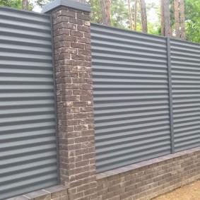 Горизонтальное расположение листа на заборе с кирпичными столбами