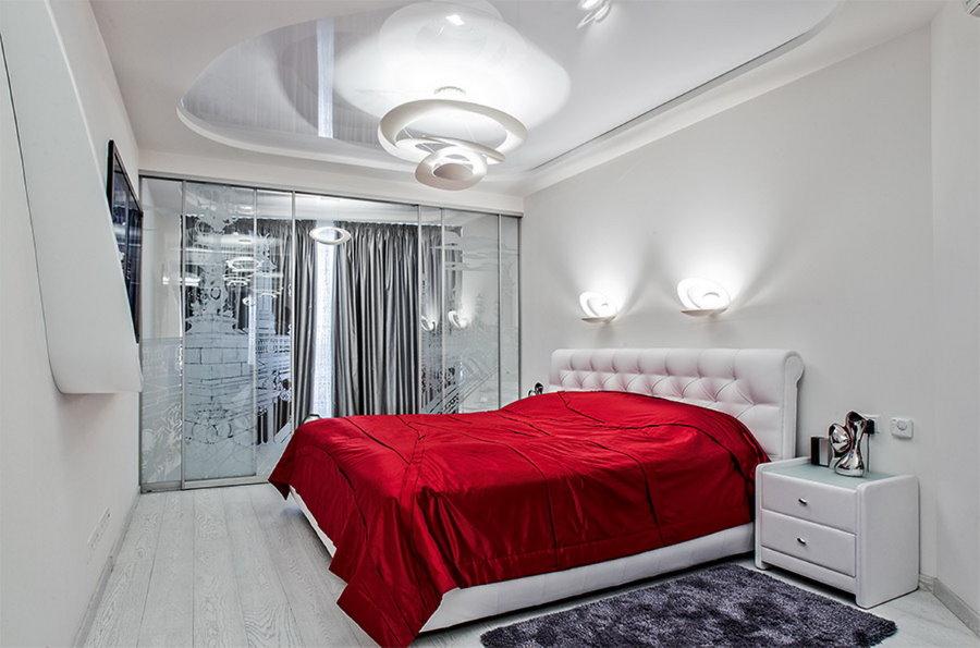 Бардовое одеяло на кровати в спальне современного стиля