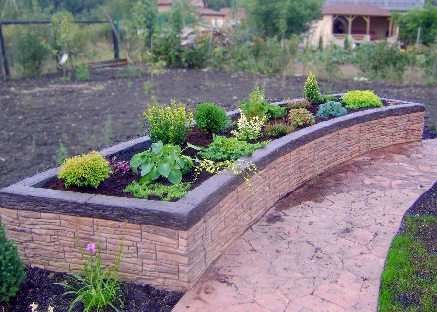 Бетонная клумба дугообразной формы с высаженными растениями