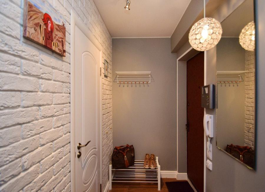 Декоративные кирпичики на стене узкого коридора