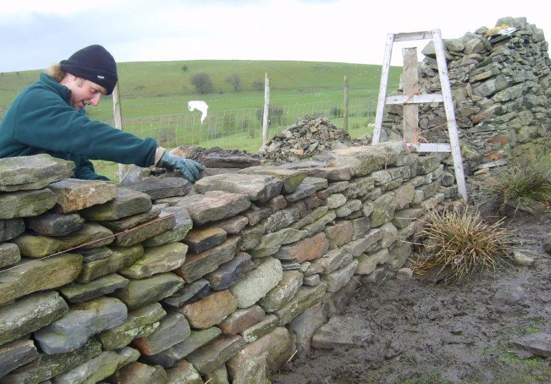 Кладка каменного забора на загородном участке