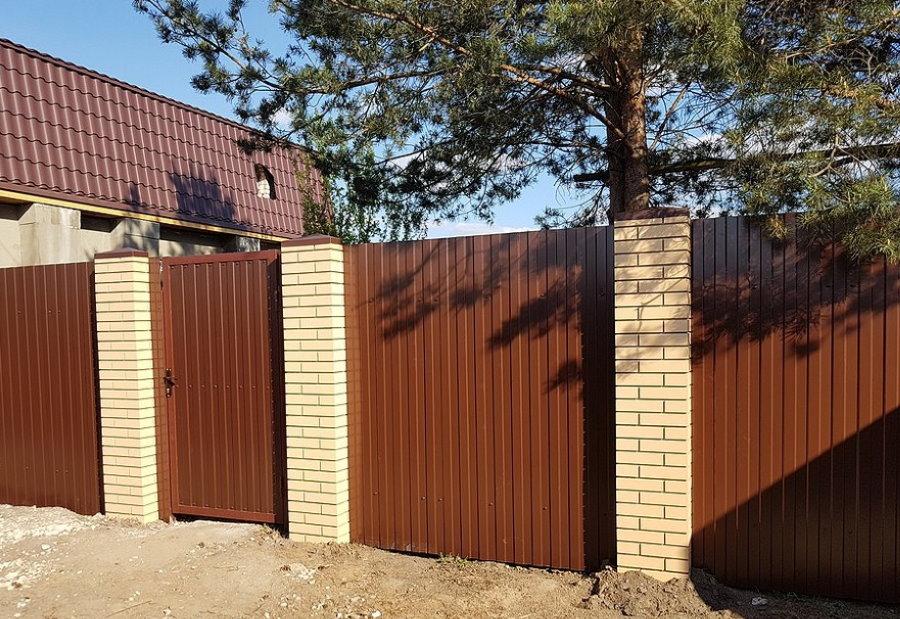 Контрастный забор из профнастила на кирпичных опорах