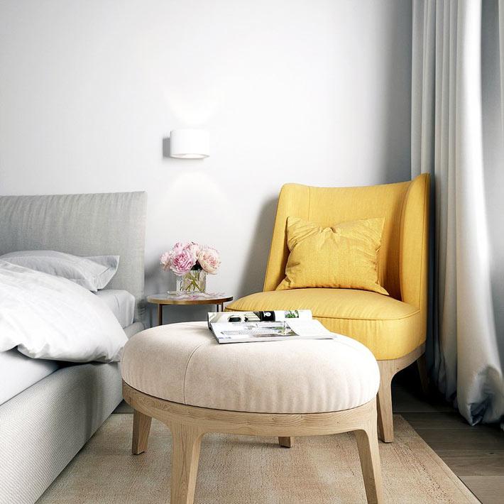 Небольшое кресло желтого цвета в углу спальни