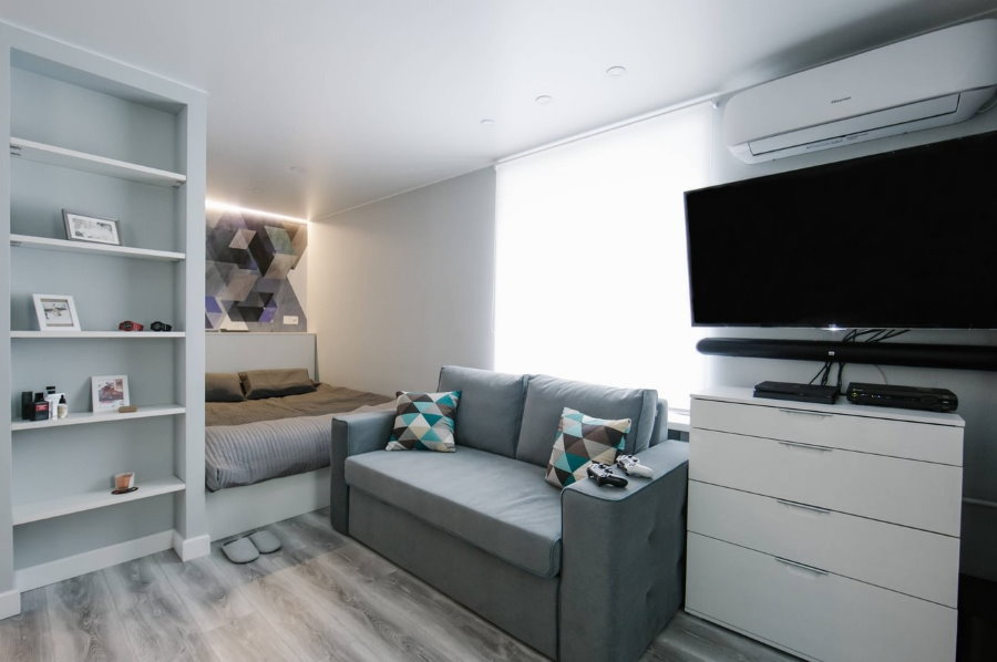 Телевизор на белом комоде с выдвижными ящиками