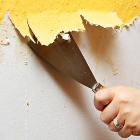 Снятие шпателем старой краски со стен в прихожей