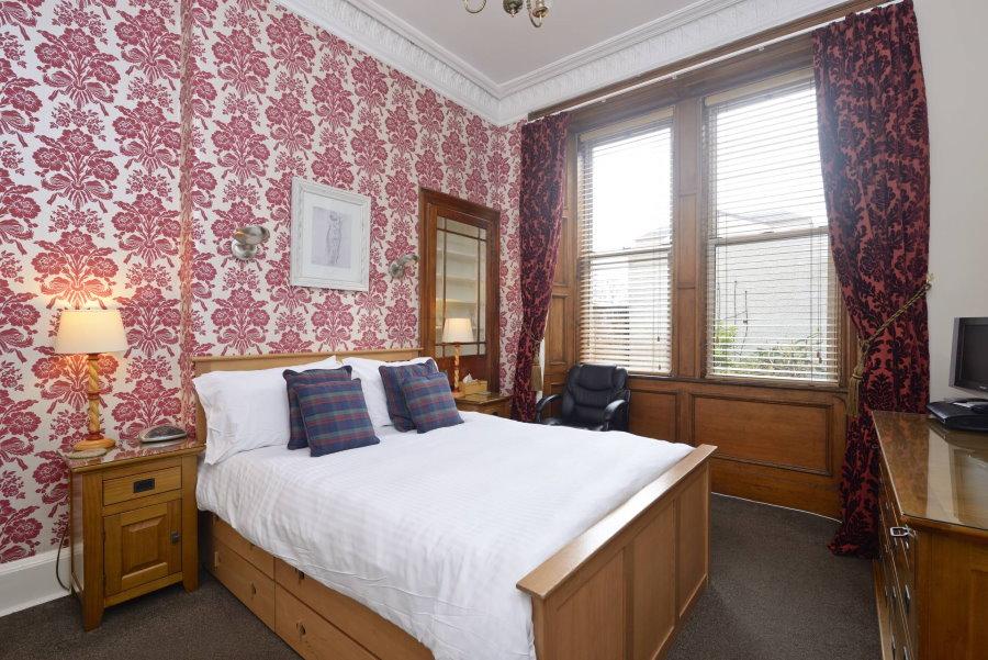 Удобная кровать для гостей в комнате с красивыми обоями