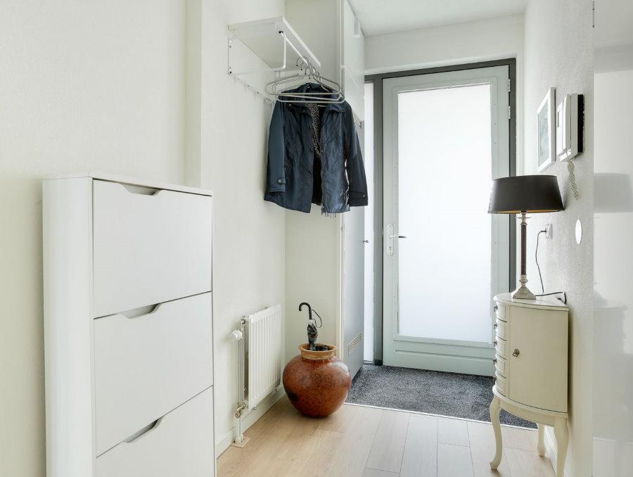 Узкая обувница белого цвета в длинном коридоре