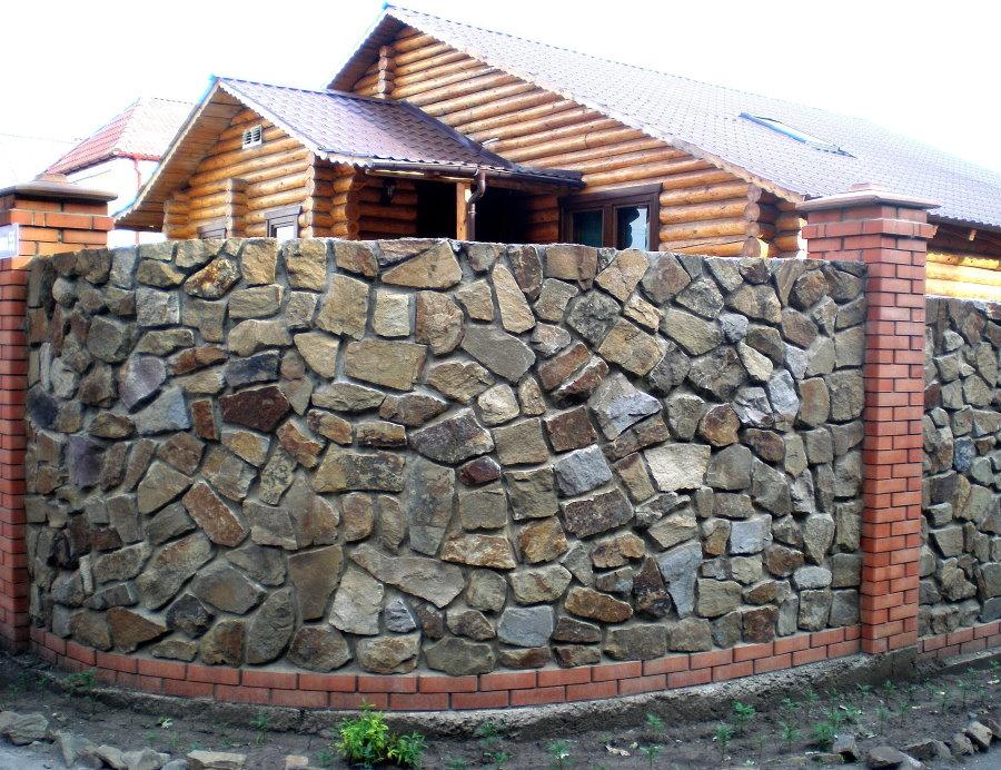 Массивный забор из камня на кирпичных столбах