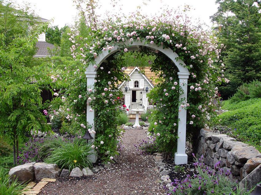Белая арка из дерева над гравийной дорожкой