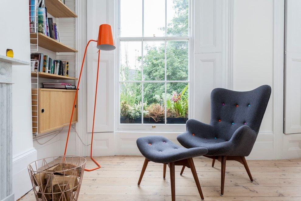 Серое кресло перед окном гостиной комнаты