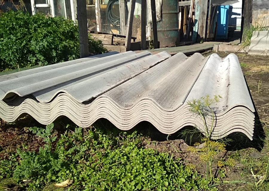 Стопка волнового шифера во дворе частного дома