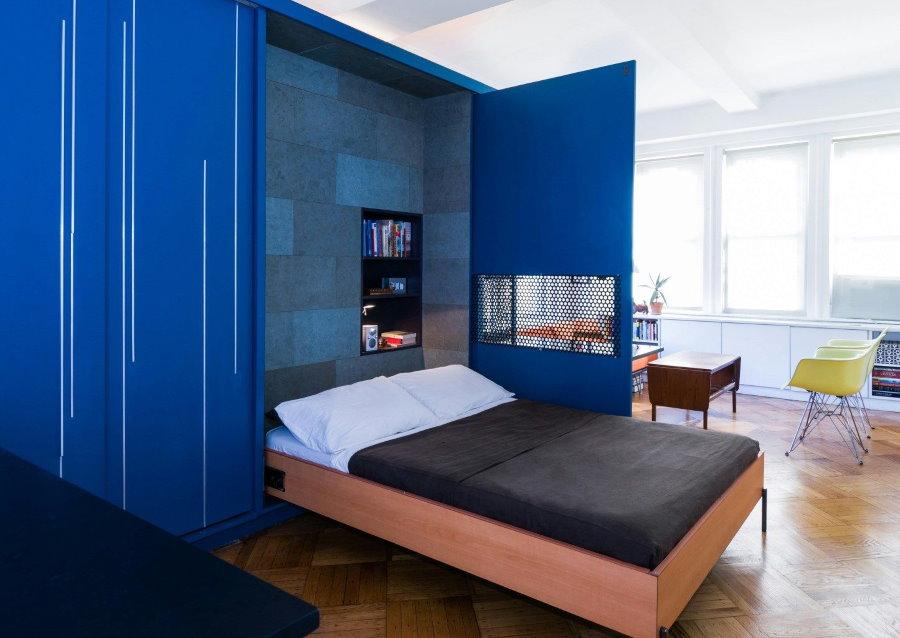 Синий шкаф с откидной кроватью в гостиной комнате