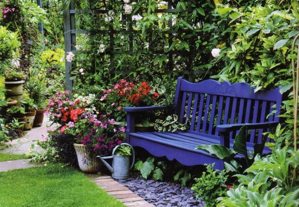 Синяя скамейка из дерева возле деревянной шпалеры