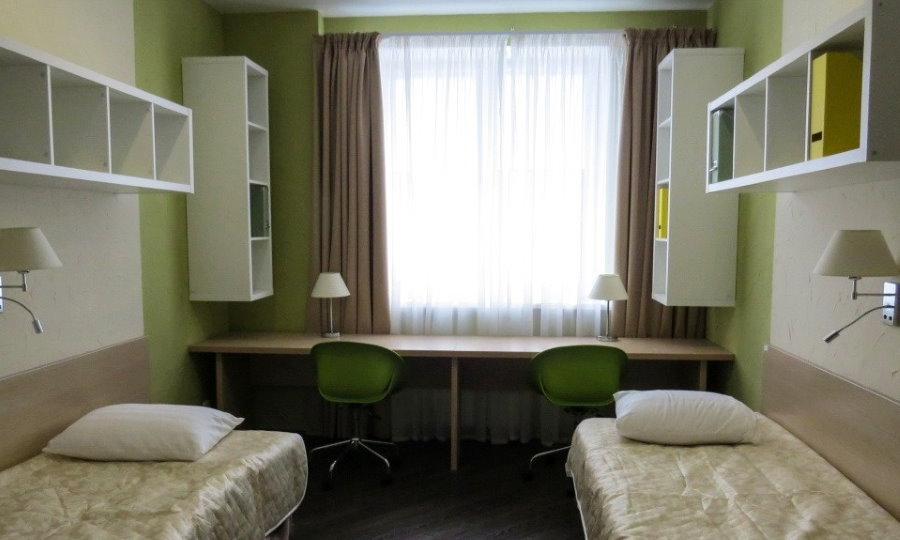 Письменный стол на двоих перед окном комнаты