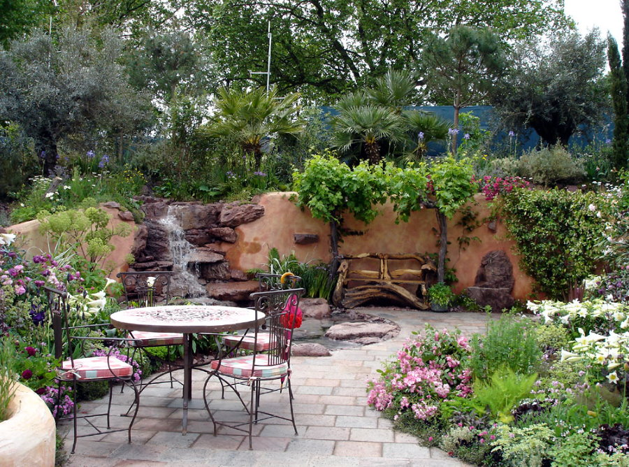 Обеденный столик на площадке для отдыха в небольшом саду