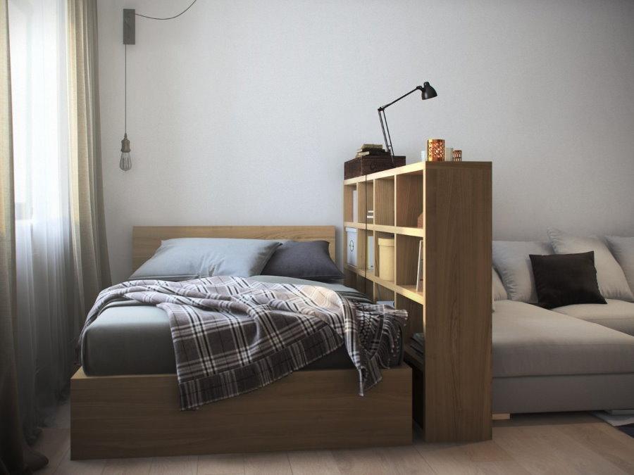 Спальное место за стеллажом в гостиной комнате