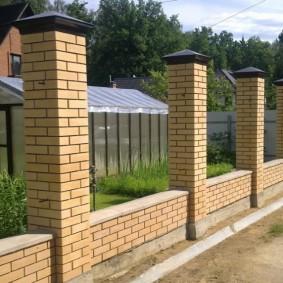 Кирпичные столбы забора на бетонном фундаменте