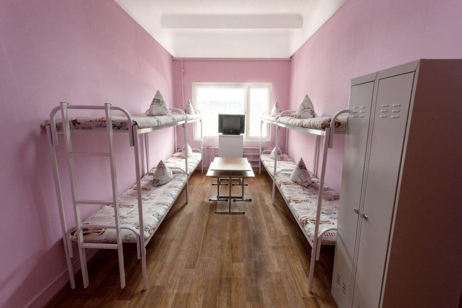 Розовые стены в узкой комнате для студенток