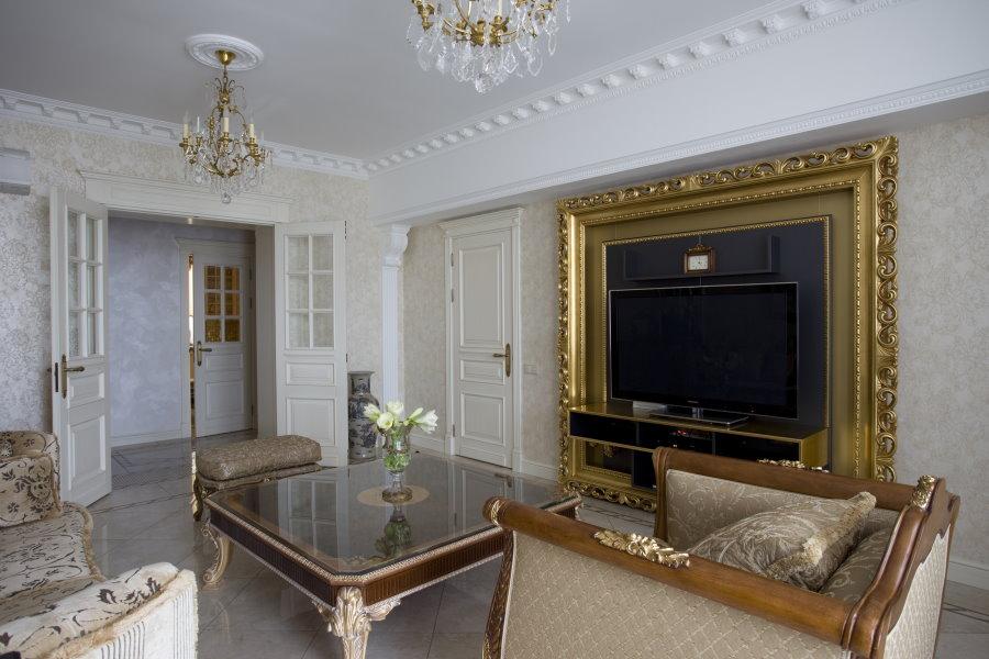 Телевизор в рамке с позолотой на стене гостиной
