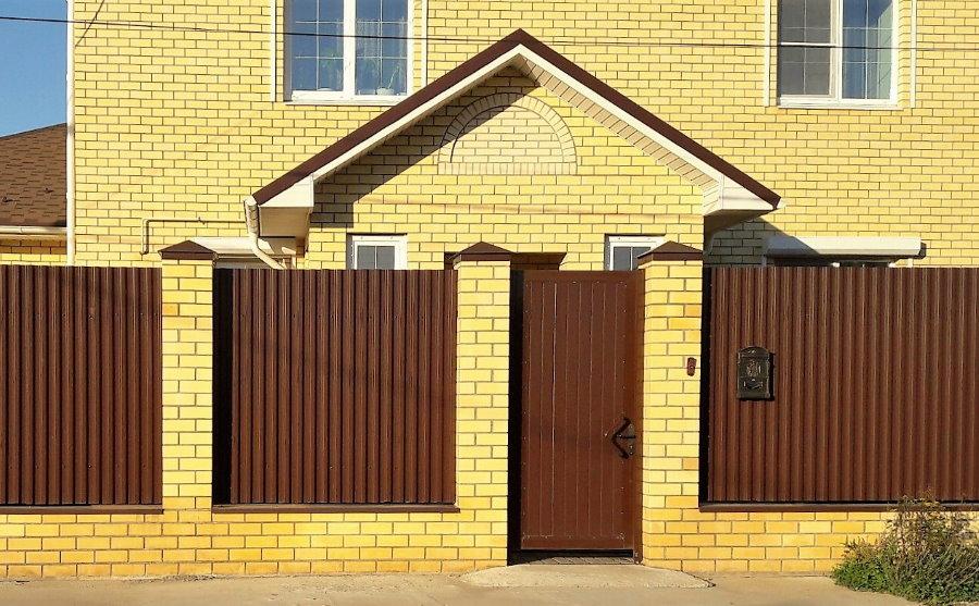 Забор из профлиста перед кирпичным домом