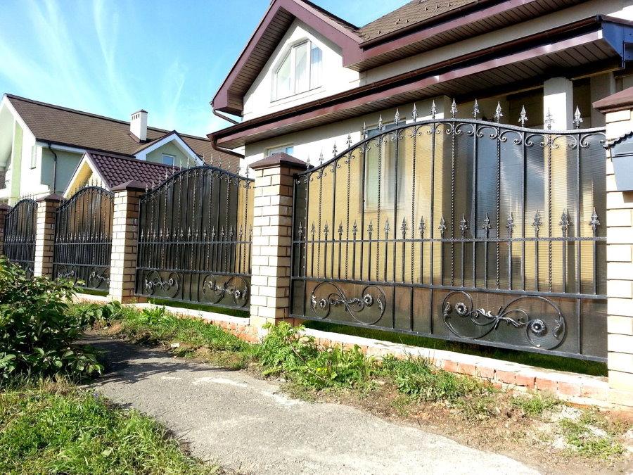 Красивый забор с ковкой на кирпичных колоннах