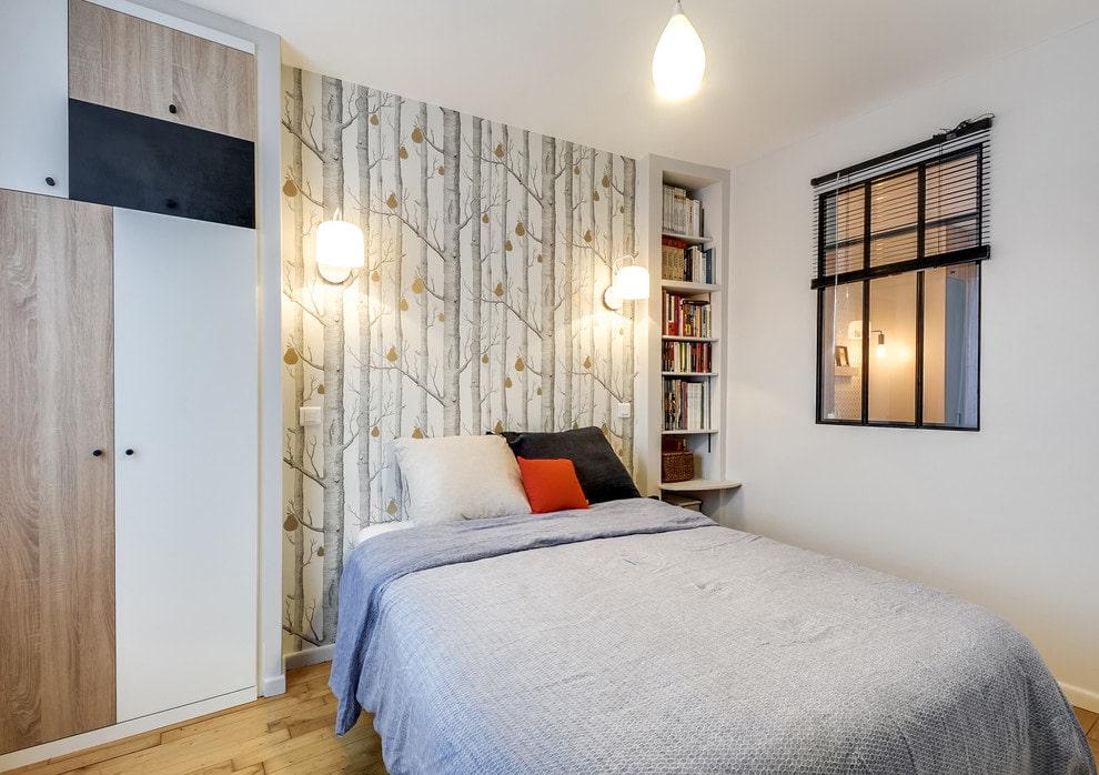 Обои с рисунками деревьев на стене за кроватью