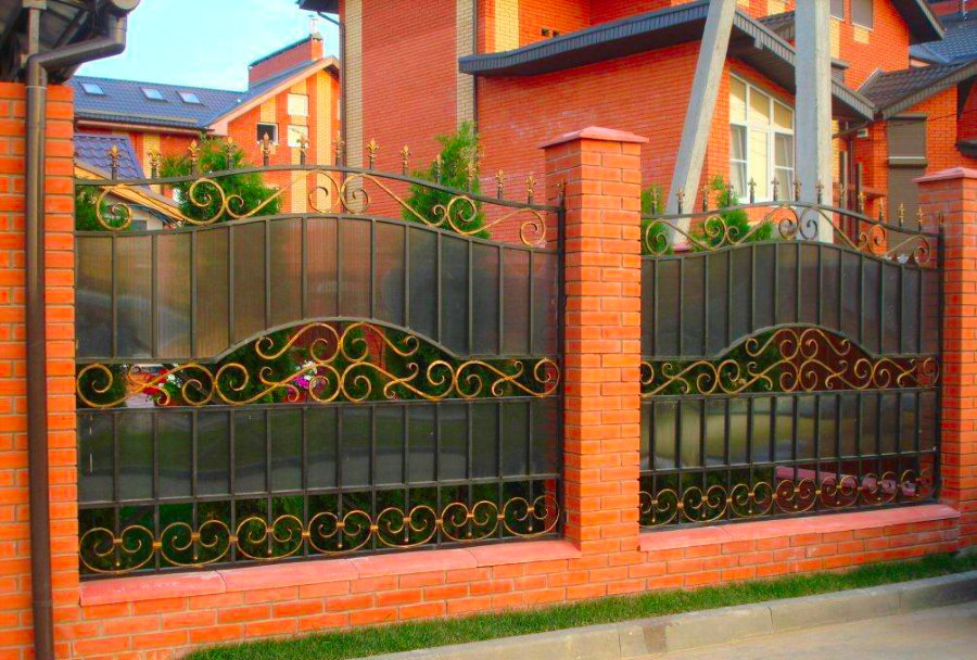 Красивый забор на кирпичных столбах с ковкой и поликарбонатом
