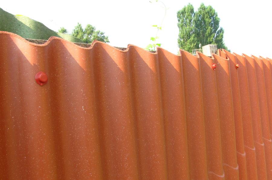 Скошенные края волнового шифера на дачном заборе