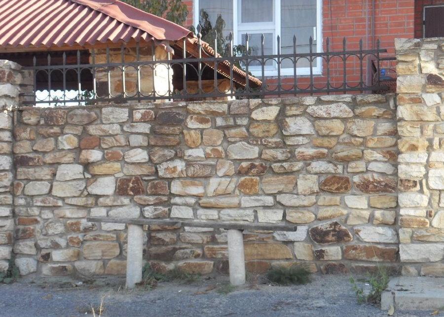 Массивная ограда из бутового камня перед загородным домом