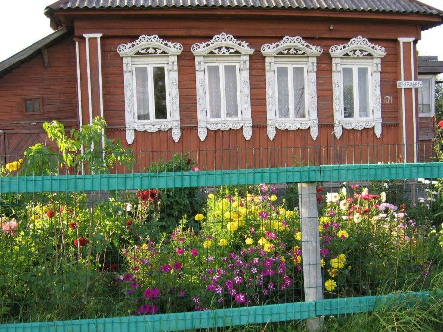 Простой забор из сетки в палисаднике сельского дома