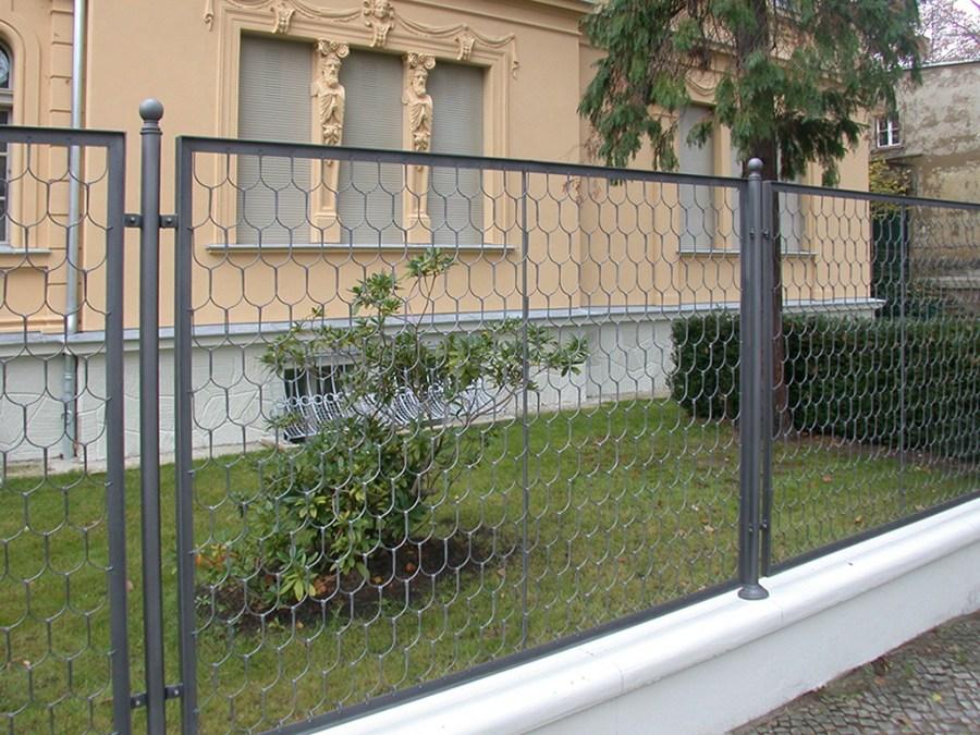 Сетчатый забор в палисаднике перед кирпичным домом
