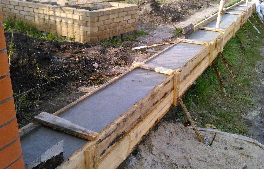 Заливка бетонного фундамента для забора с кирпичными столбами