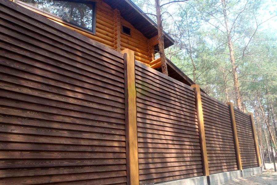 Сплошная ограда из деревянных жалюзи на дачном участке