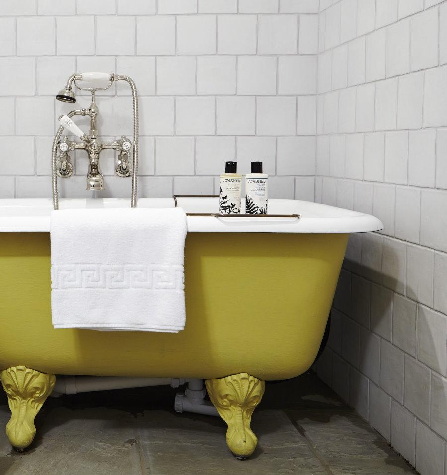 Желтая ванна в комнате с белой плиткой