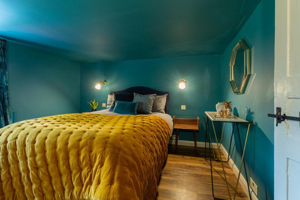 Желтое одеяло в спальне с бирюзовыми стенами