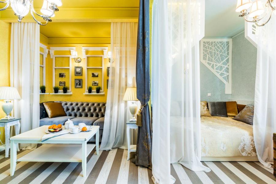 Зонирование комнаты шторами и цветом стен