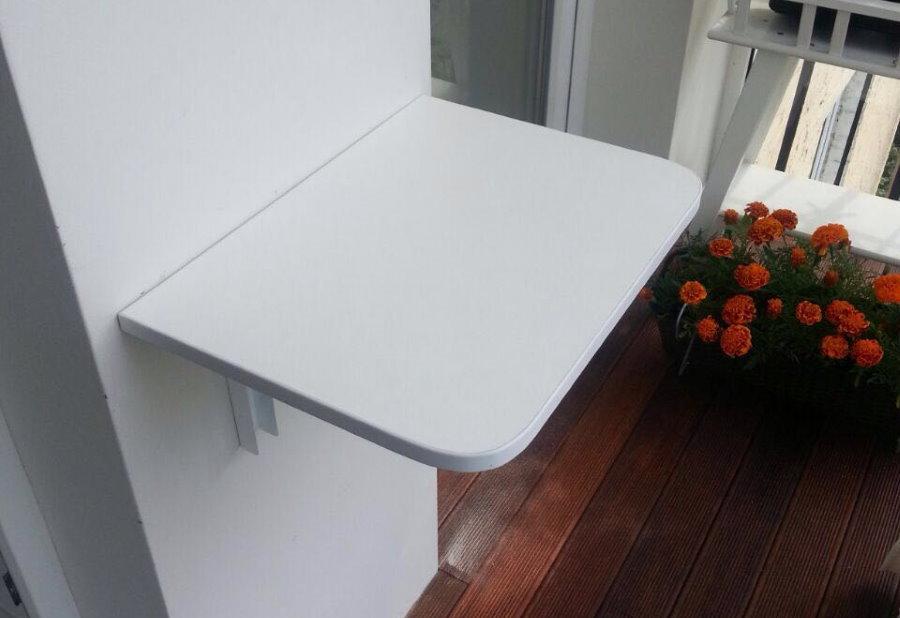 Откидной столик из белого пластика на стене лоджии