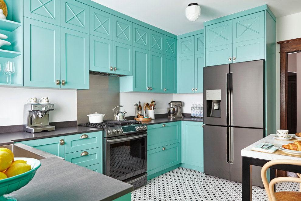 Серый холодильник на кухне с бирюзовой мебелью
