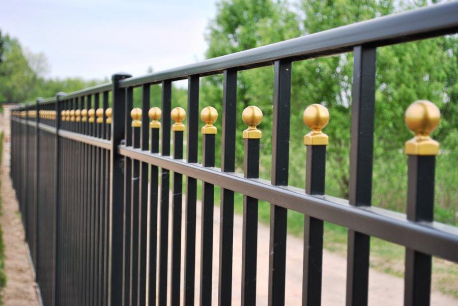 Золотистый декор на заборе из профильных труб