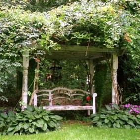 Старая скамейка под заросшей перголой