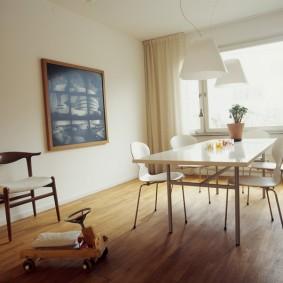 Обеденный стол в комнате с белыми стенами