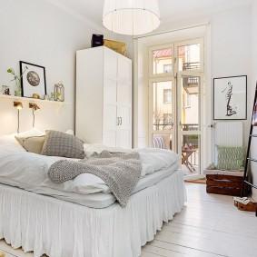 Белый шкаф у окна спальной комнаты