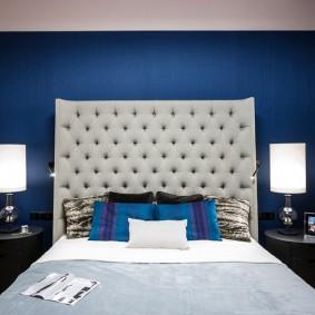 Синяя стена за мягким изголовьем кровати