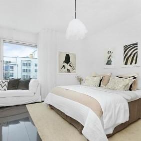 Широкая кровать в спальне с белой отделкой
