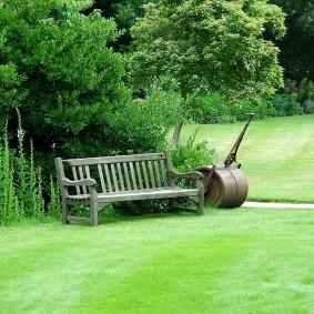 Каток для укатывания земли около деревянной скамейки