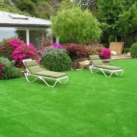 Садовые шезлонги на зеленом газоне